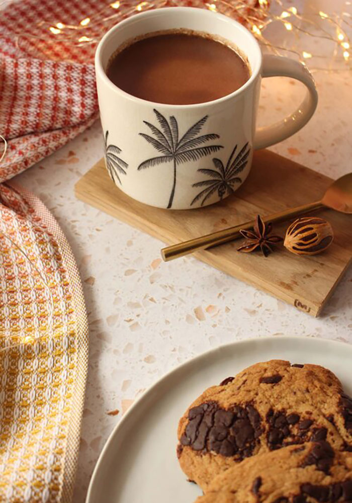 Image of cocoa tea in a white mug with a chocolate chip cookie