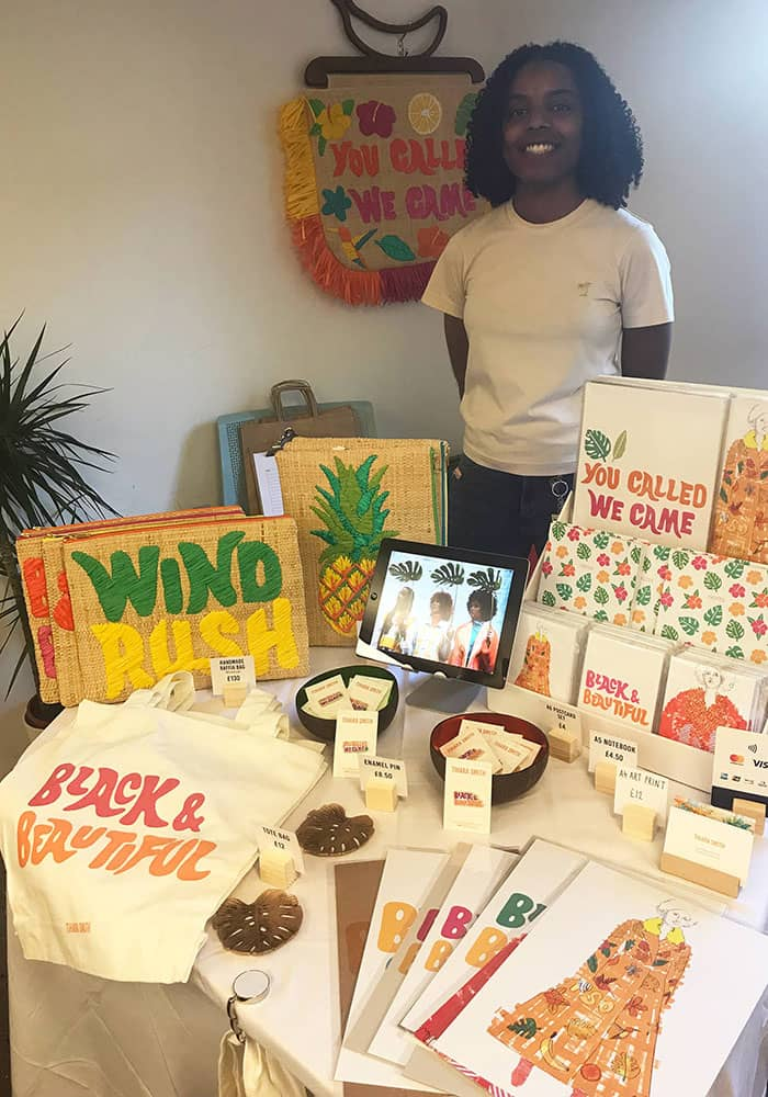 Tihara Smith at Black Culture Pop-Up Market: Windrush Special, Impact Brixton. The table display includes prints, tote bags and raffia bags from the collection.