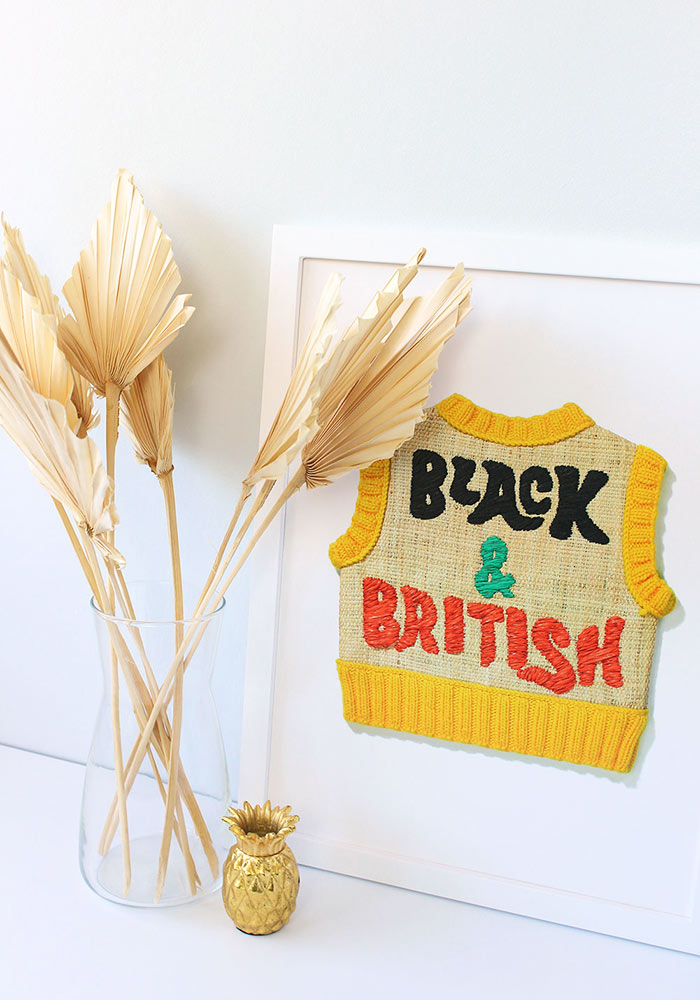 Image of Black and British vest print in a white frame on a table