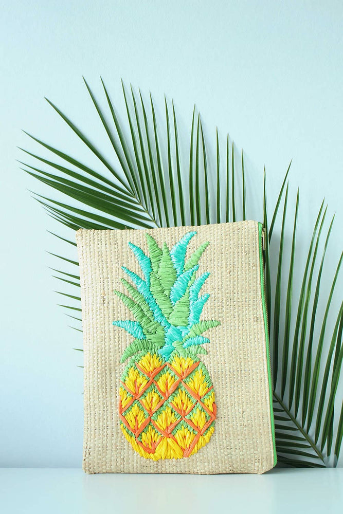 A hand-embroidered raffia clutch bag  with a pineapple motif in bright yellow, green and turquoise. Featured also is a leaf which the bag is leaning on in the picture.
