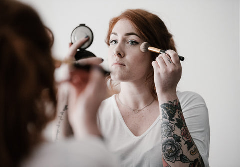 Freckled women putting on makeup