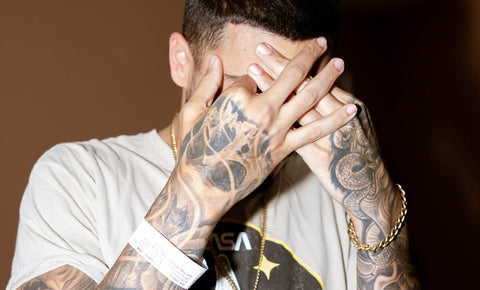 Tattooed man covering face