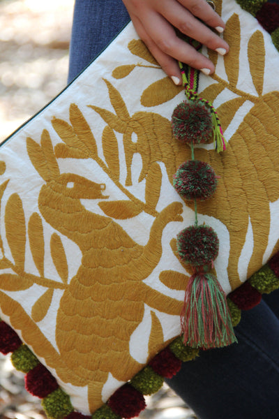 A Gold Otomi clutch with pompoms and hand embroidered tassels