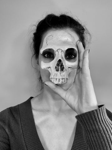 black and white photograph of woman holding a fake skull over her face.