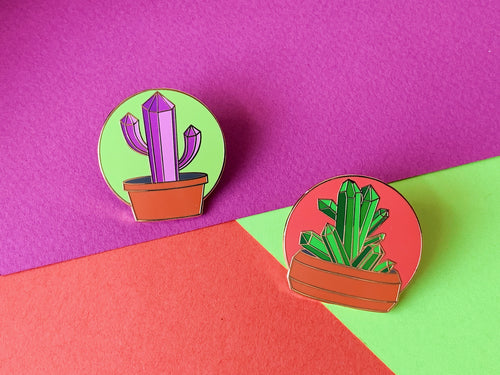 Picture shows both pins on a colour coordinating background. On the left a purple cactus in a pot with a green circle background, on the right a green succulent made of crystal points in a pot and a pinky orange circular background.