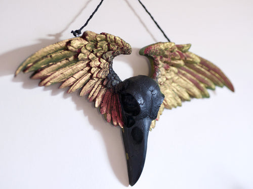 3D hanging art piece of a black raven skull with colour shifting feathery wings spread to either side.
