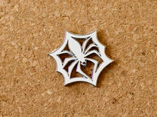 Load image into Gallery viewer, White enamel pin in the shape of a paper snowflake that looks like a spider in a web.