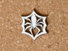 Load image into Gallery viewer, White enamel pin in the shape of a paper snowflake that looks like a spider in a web