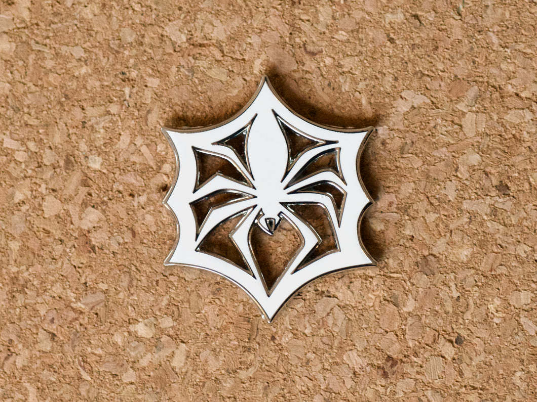 White enamel pin in the shape of a paper snowflake that looks like a spider in a web