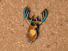 Load image into Gallery viewer, Lapel pin of a deer bust with sunglasses, antlers and a beaded necklace. The antler and necklace are alternating colours of the Transgender Pride flag (blue, pink, white, pink, blue)