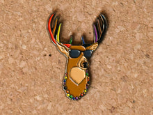 Load image into Gallery viewer, Lapel pin of a deer bust with sunglasses, antlers and a beaded necklace. The antler and necklace are alternating colours of the POC inclusive Pride flag (red, orange, yellow, green, blue, purple, brown, black).