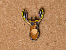 Load image into Gallery viewer, Lapel pin of a deer bust with sunglasses, antlers and a beaded necklace. The antler and necklace are alternating colours of the non binary pride flag (yellow, white, purple, black)