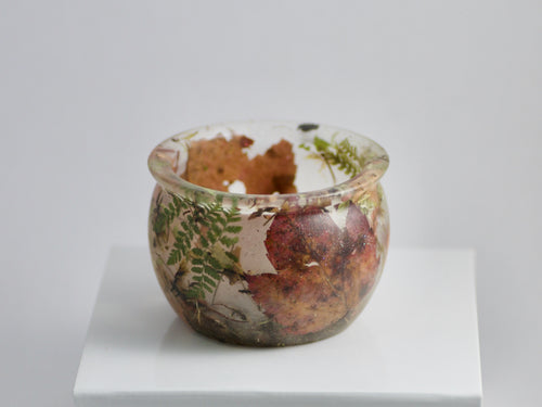 A clear resin cauldron filled with ferns, moss, and dried leaves.