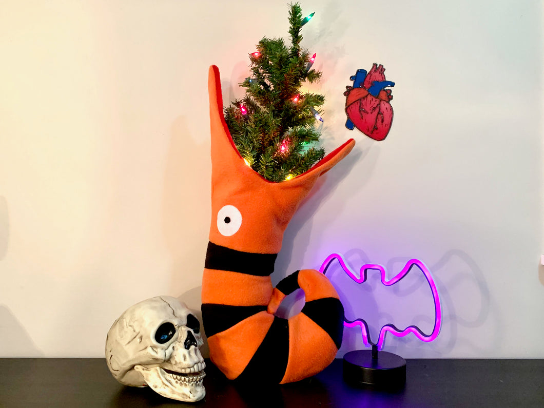 Picture of Christmas stocking that looks like an orange and black striped snake with a Christmas tree in its mouth.