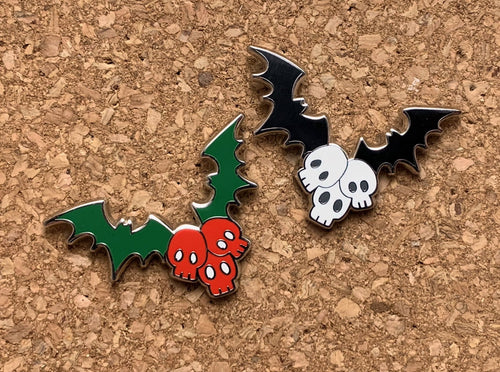 Both pins side by side. The black and white version and the red and green Christmas version.