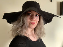Load image into Gallery viewer, Picture of a woman wearing a wide brimmed black hat with a brim shaped like a spider web.