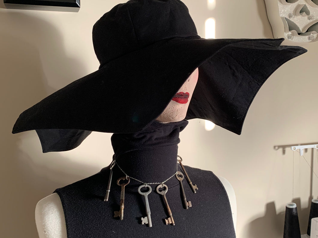 Photo of wide brimmed black hat on a mannequin. The hat has several points on the brim that looks like a spider web
