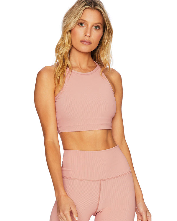 Model wearing pink ribbed activewear tank and high waist leggings
