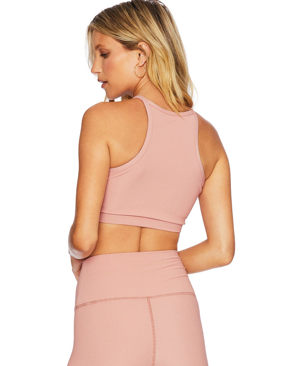Back of model wearing pink ribbed activewear tank and high waist leggings