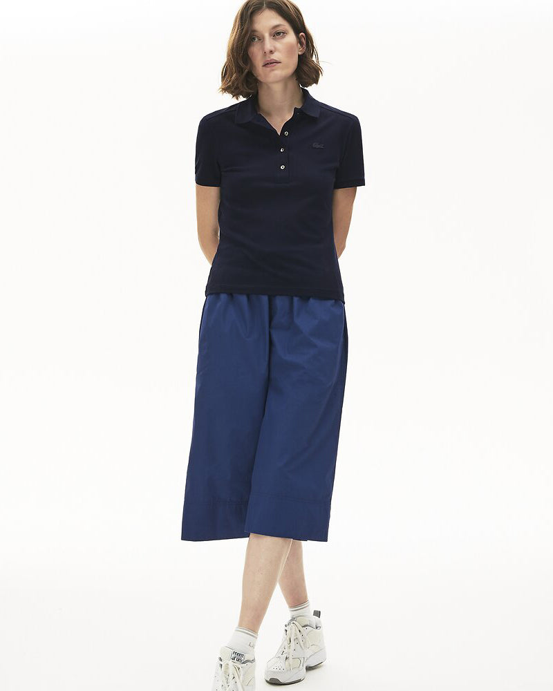 Front full length view of model wearing Lacoste classic 5 button slim fit polo in navy blue with blue alligator