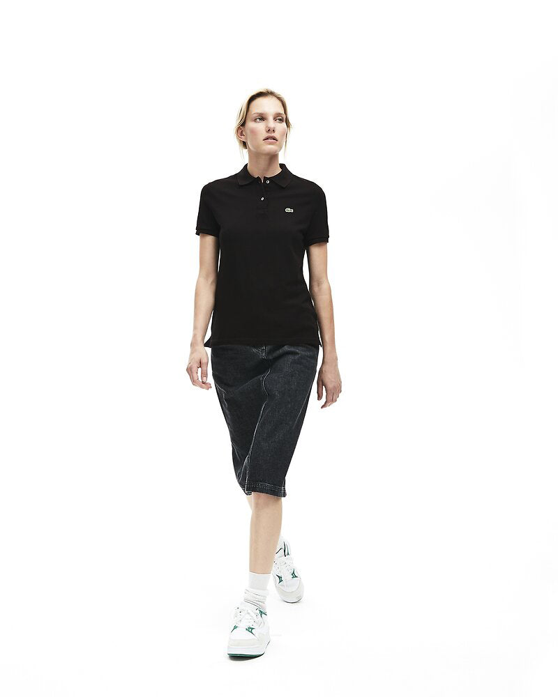 Full length view of model wearing Lacoste classic 2 button relaxed fit polo in black with green alligator