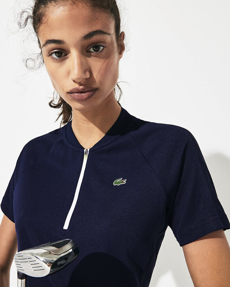 Close up front view of model wearing Lacoste Golf waffle polo in navy with white half zip and green alligator on chest