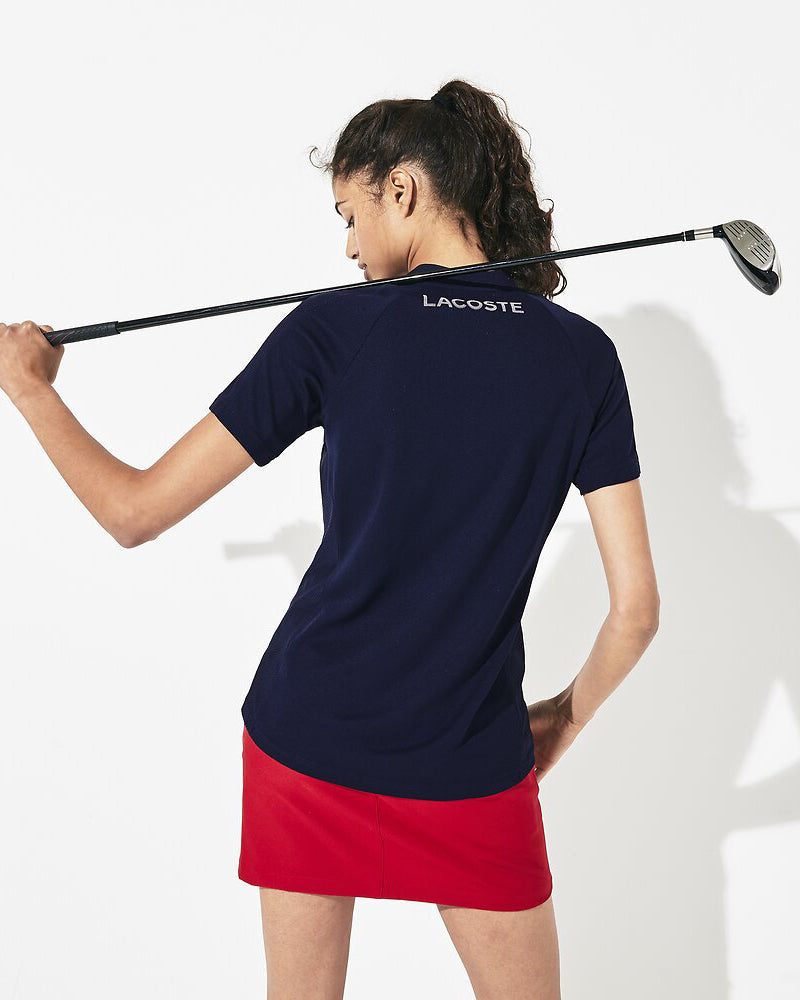 Back view of model wearing Lacoste Golf waffle polo in navy with white half zip and green alligator on chest