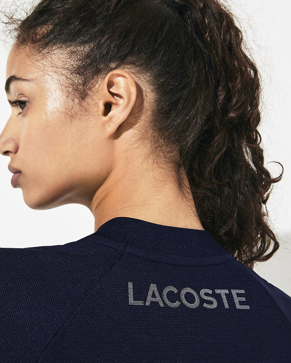 Back view of model wearing Lacoste Golf waffle polo in navy with lacoste written across back of shoulders