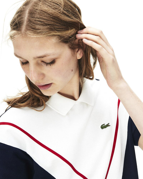 Close up front view of model wearing lacoste mif technical pique polo in navy and flour with green alligator on chest