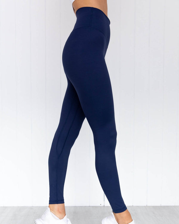 Side view of model wearing midnight navy panther high rise full length legging