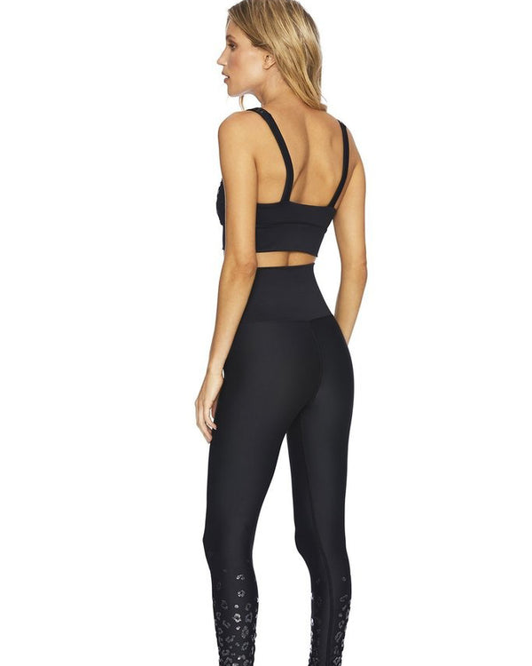 Back of model wearing black leopard sports bra and high waist leggings