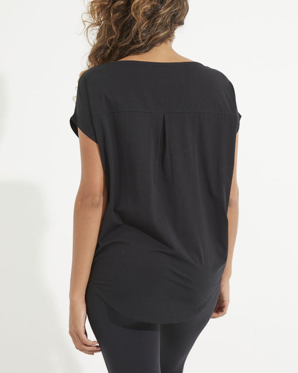 Back of model wearing black short sleeve tee with a back pleat detail