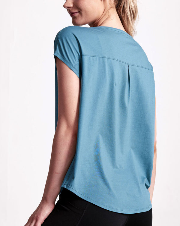 Back of model wearing teal short sleeve tee with back pleat detail