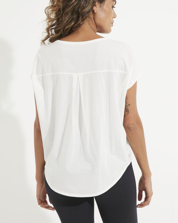 Back of model wearing white short sleeve tee with back pleat detail