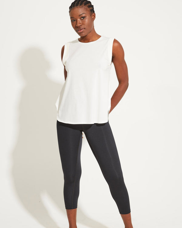 Model wearing white tank and black activewear leggings