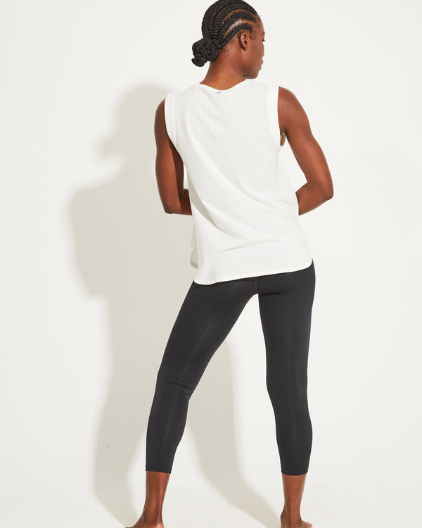 Back of model wearing white tank and black activewear leggings