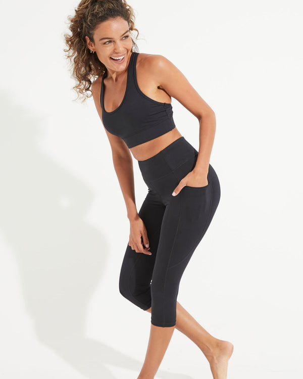Model wearing black activewear bra with black high waist crop leggings with a side pocket