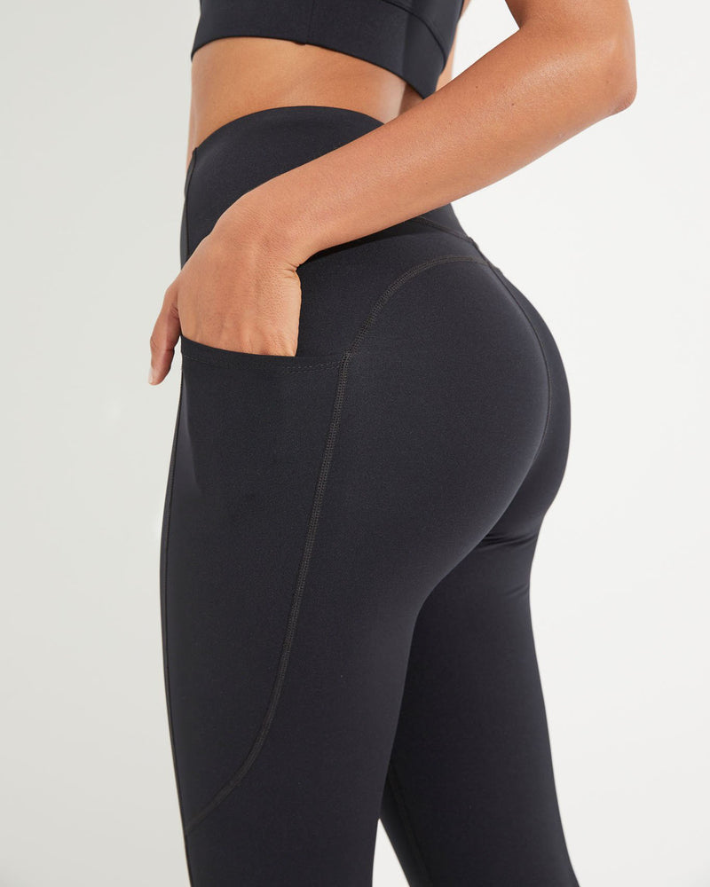 Model wearing black high waist activewear leggings with side pocket