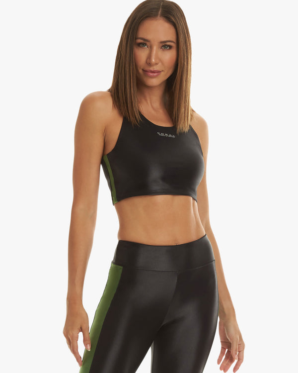 Model wearing activewear sports bra and leggings in black with a green strip down the seam