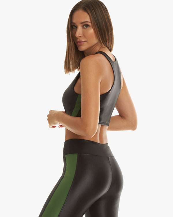 Side of model wearing black activewear sports bra and leggings with a green strip down the seams