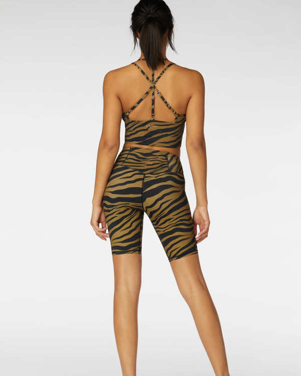 Back of model wearing activewear crop and shorts set in black and brown tiger print