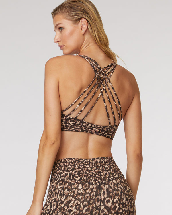 Back view of model wearing  l'urv hybrid crop in cinnamon showing criss cross back