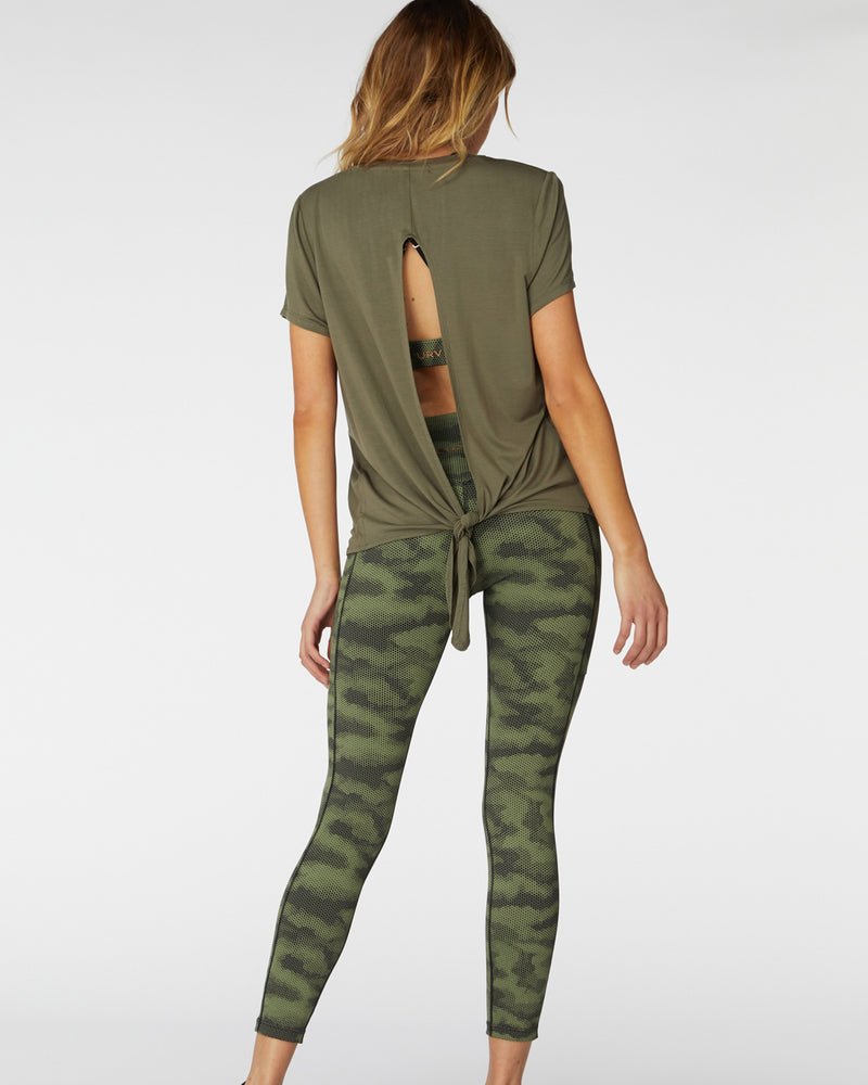 Back view of model wearingl'urv radiant tee in fern tied at back