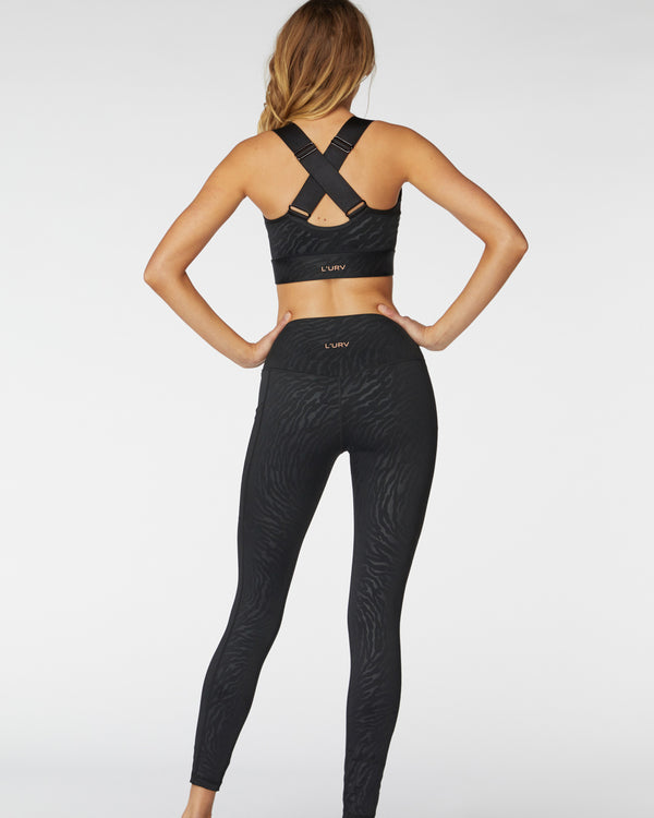 Back view of model wearing  l'urv step up crop in black with matching leggings