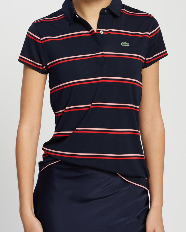 Front view of model wearing Lacoste golf striped jersey polo in navy blue and prince and green alligator on chest
