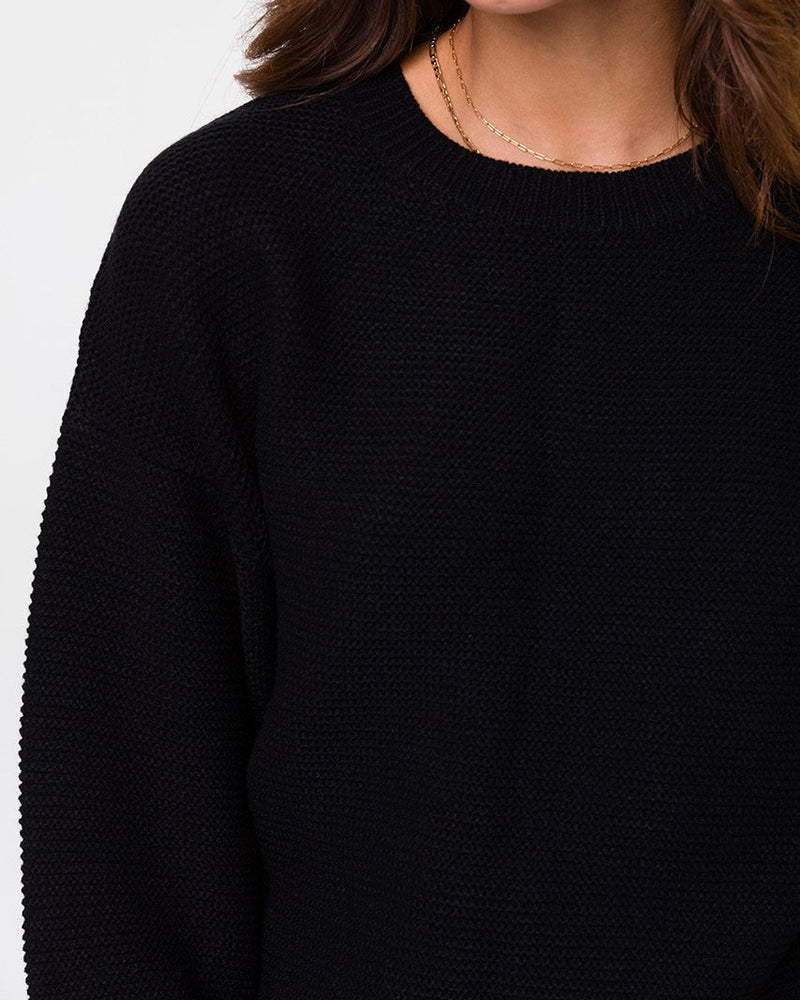 Close up of model wearing black knit sweater