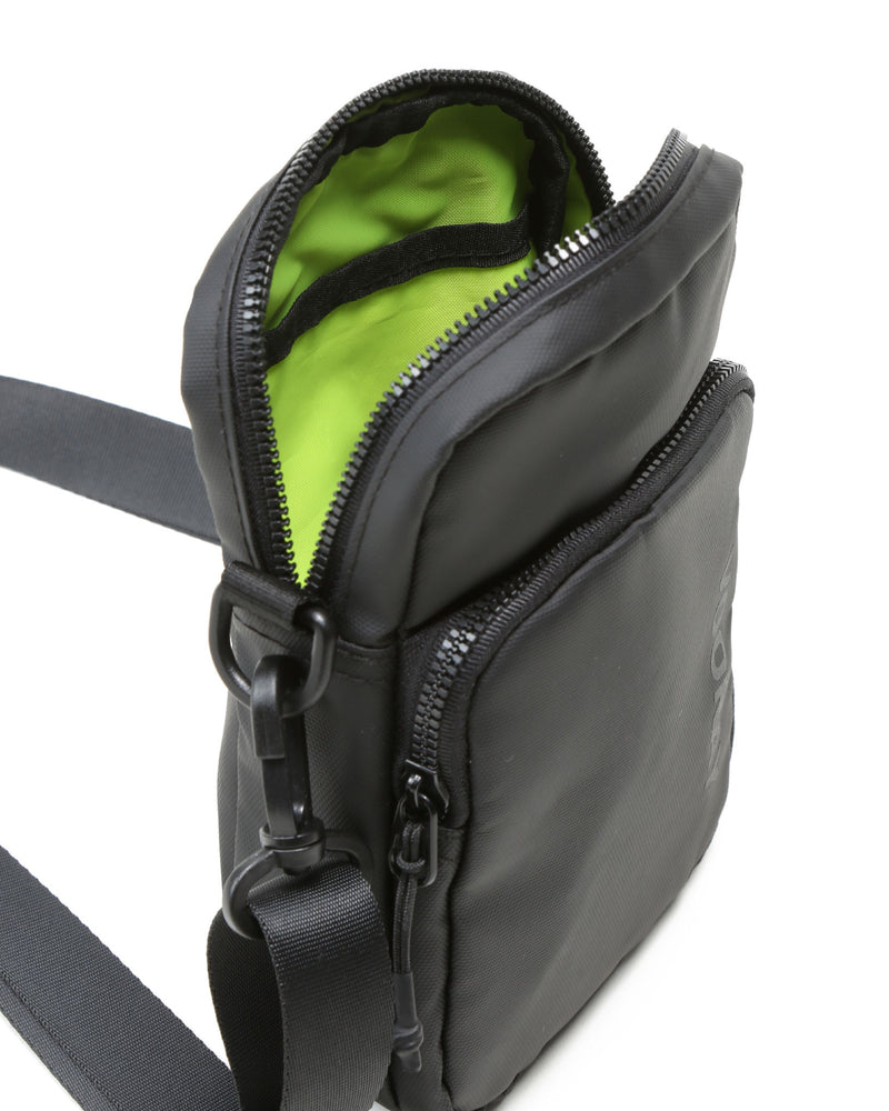 Top zip opened to show green lining of core crossbody bag in black