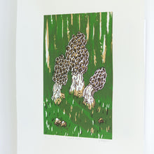 Load image into Gallery viewer, A side, angled view of a small screenprint of three morel mushrooms on a dark green background. The print is made up of three colours, an emerald green, a light brown, and a dark brown. The print is small on the paper, with large white borders around it.
