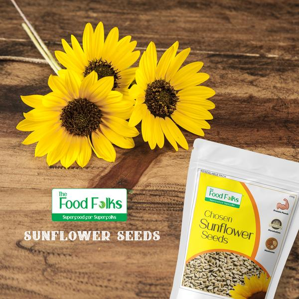 sunflower seeds in a pack with sunflowers on a wooden background