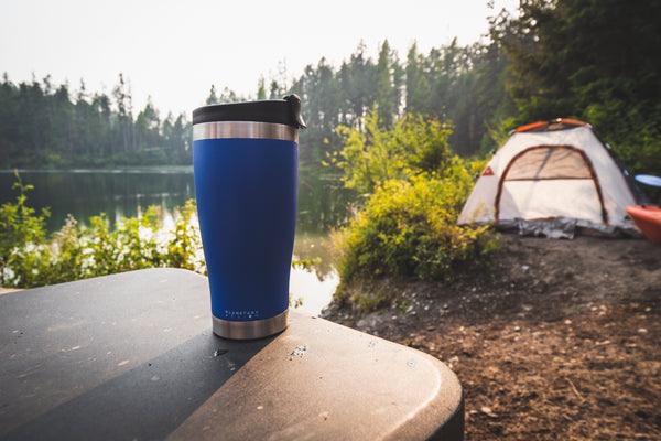 blue adventure tumbler on camp table facing sunset and camping tent